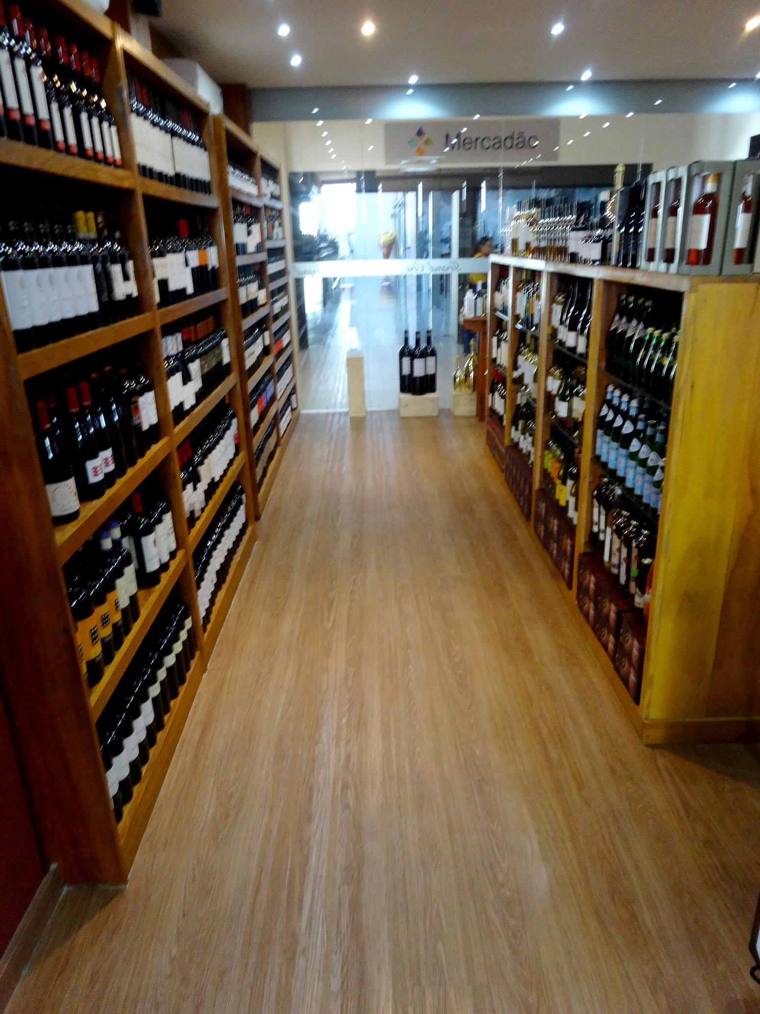 Piso vinílico rústico decora loja de vinhos