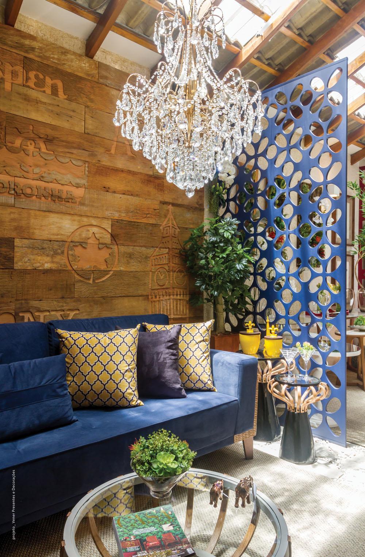 Painel de madeira de demolição reveste a parede e biombo de MDF divide ambientes com charme; ambos da marca Mentha